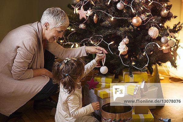 Großmutter hilft Enkelin beim Schmücken des Weihnachtsbaums zu Hause