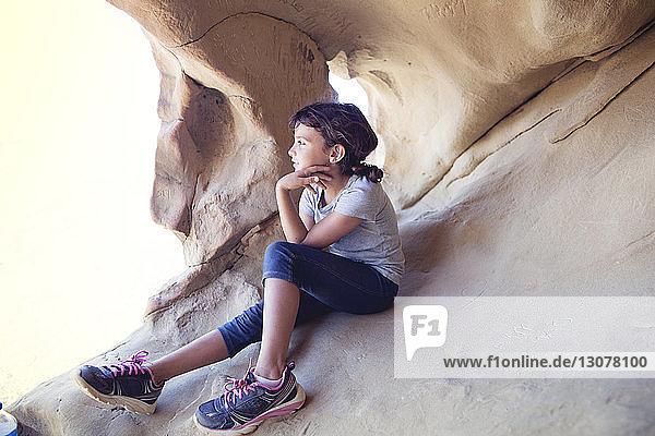 Nachdenkliches Mädchen sitzt in Höhle