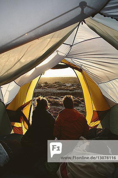 Rückansicht von Freunden  die im Zelt sitzen