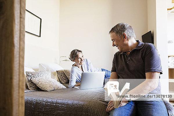 Glücklicher älterer Mann sieht Frau an  die einen Laptop im Schlafzimmer benutzt