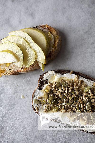Hochwinkelansicht von geröstetem Brot mit Kürbiskernen und Birnen auf dem Tisch