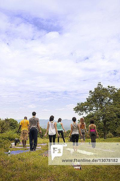 Rückansicht von Freunden beim Training im Stehen auf dem Feld vor bewölktem Himmel