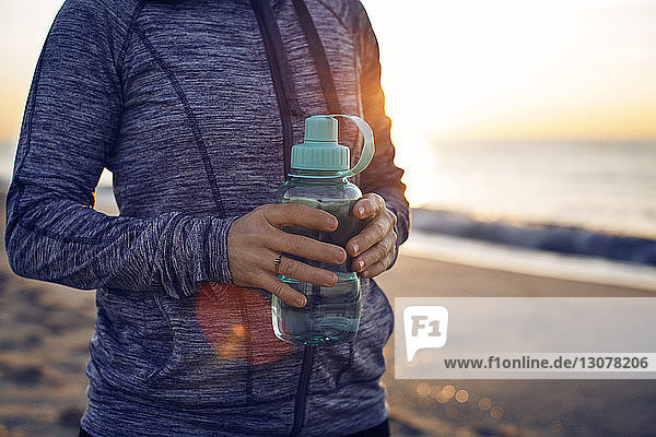Midsection of woman with water bottle standing at beach