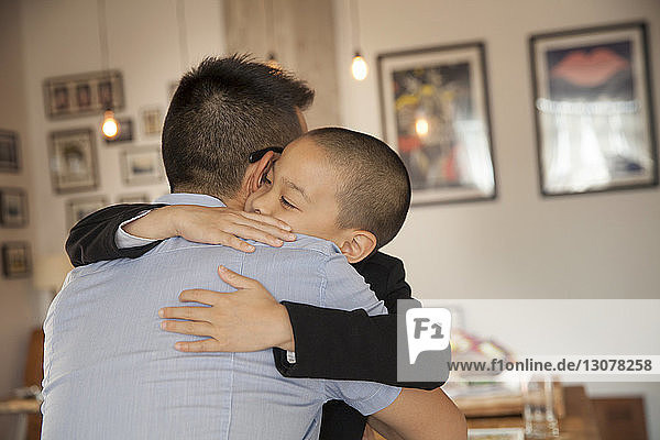 Son embracing father at home