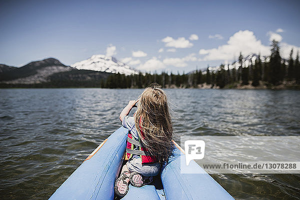 Rear view of girl sitting in inflatable raft on lake