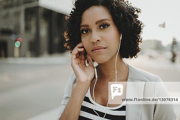 Nahaufnahme-Porträt einer Frau  die Musik hört  während sie auf der Straße der Stadt steht