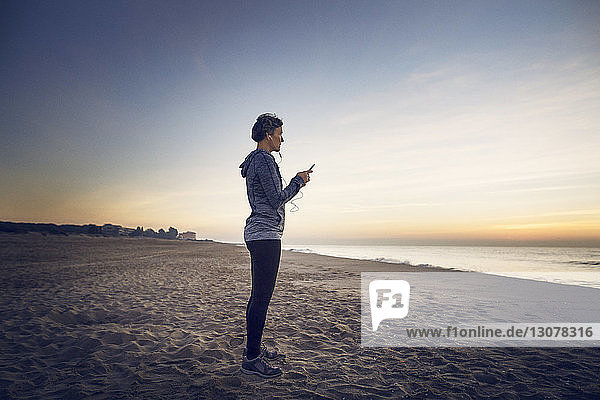 Full length of woman using phone while standing at beach
