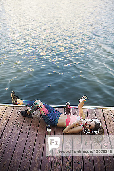 Smiling woman lying and clicking selfie on wooden walkway at riverbank