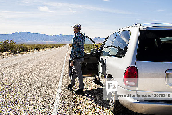 Full length of man standing by car on road at desert during sunny day