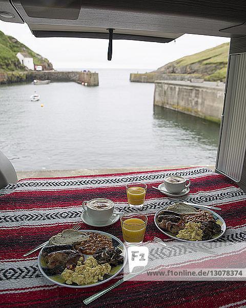 Schrägaufnahme der im Wohnmobil servierten Speisen gegen das Meer
