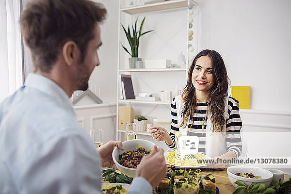 Happy woman eating spaghetti pasta while looking at friend in lunch party