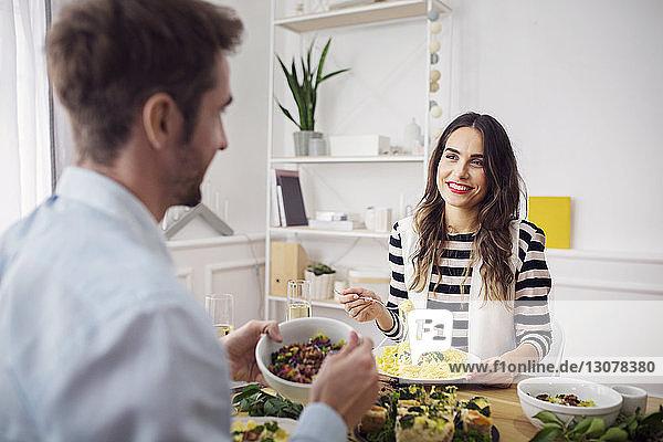Glückliche Frau isst Spaghetti-Nudeln  während sie einen Freund beim Mittagessen anschaut