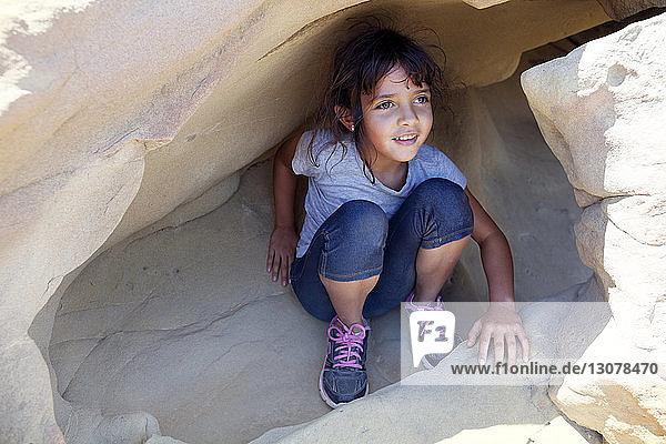 Lächelndes Mädchen in Höhle sitzend