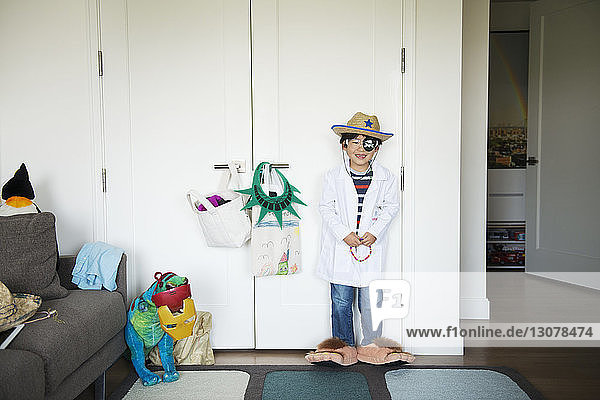 Happy boy wearing costume standing against cupboard at home