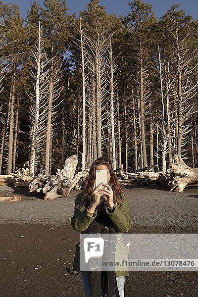 Junge Frau fotografiert mit einem Smartphone vor Bäumen am Strand