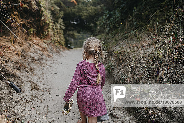 Rear view of girl walking on sand amidst trees at beach