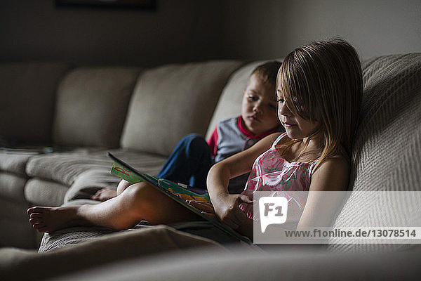 Siblings looking at picture book on sofa