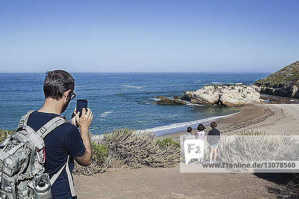 Father photographing children on beach against sky