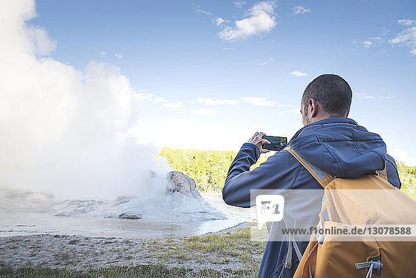 Rückansicht eines Mannes  der fotografiert  während er gegen den Himmel steht
