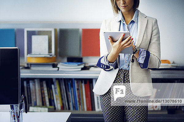 Midsection of businesswoman using tablet computer in office