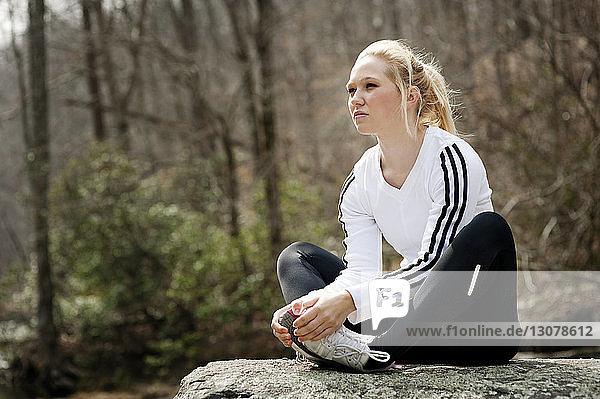 Frau übt auf Fels im Wald
