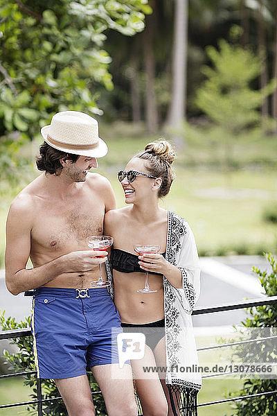 Glückliches Paar hält Getränke in der Hand  während es sich am Urlaubsort anschaut