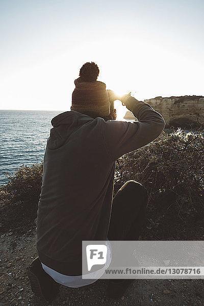 Rückansicht eines Mannes  der das Meer fotografiert  während er bei Sonnenuntergang am Strand vor klarem Himmel kauert