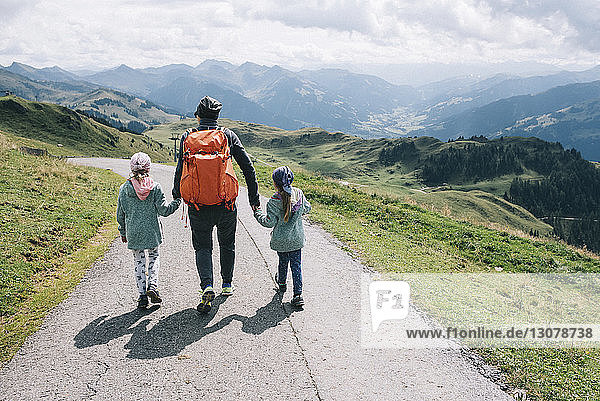 Rear view of mother with daughters walking on mountain road against cloudy sky