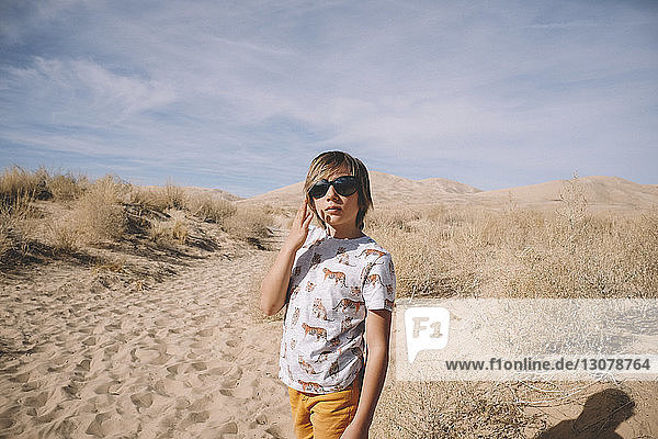 Boy wearing sunglasses while standing at desert during sunny day