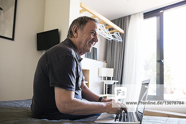 Side view of cheerful senior man looking away while using laptop in bedroom