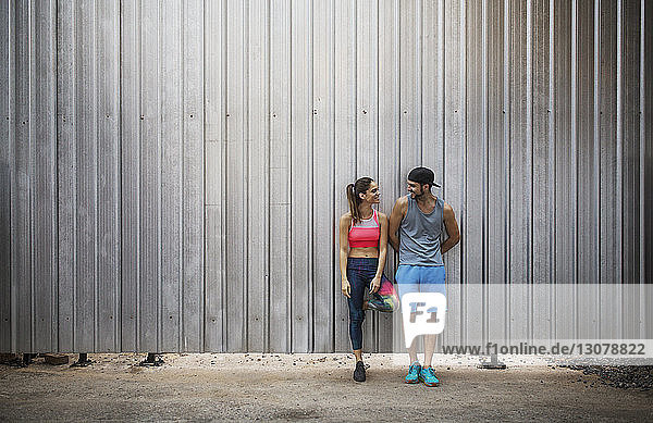 Smiling couple leaning on metal wall and talking