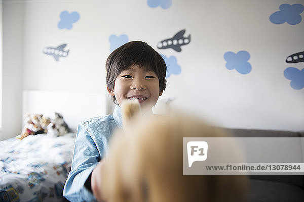 Close-up portrait of boy playing with stuffed toy at home