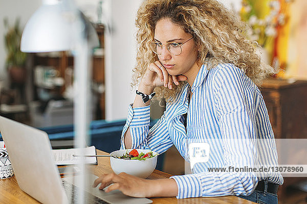 Young woman blogging through laptop computer at home office