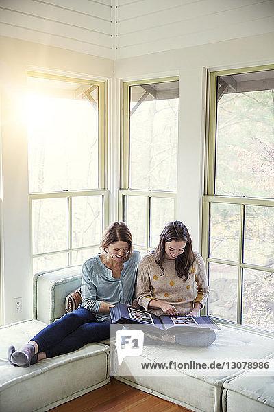 Hochwinkelansicht einer lächelnden Mutter und Tochter beim Betrachten des Fotoalbums im Wohnzimmer