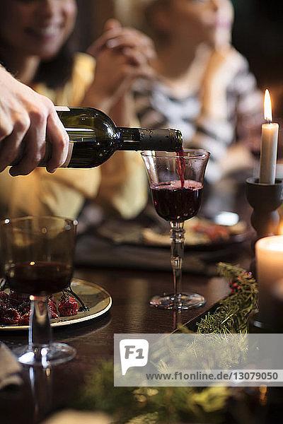 Mann gießt während der Weihnachtsfeier Wein in Glas ein