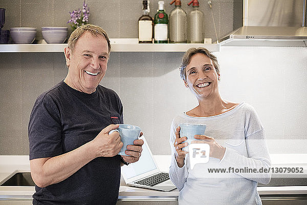 Portrait of happy senior couple holding coffee mugs in kitchen