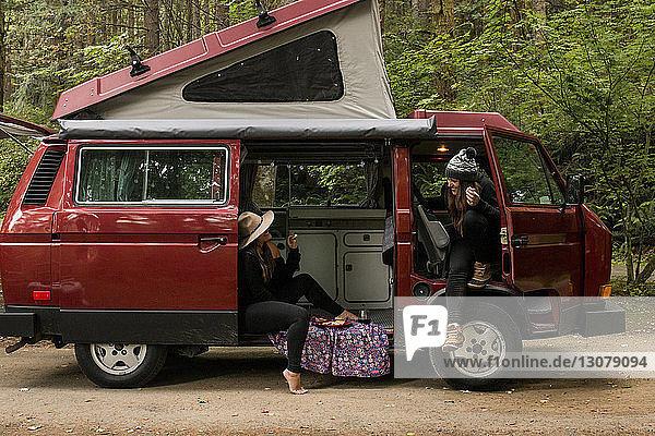 Freundinnen unterhalten sich  während sie im Wohnmobil im Wald sitzen