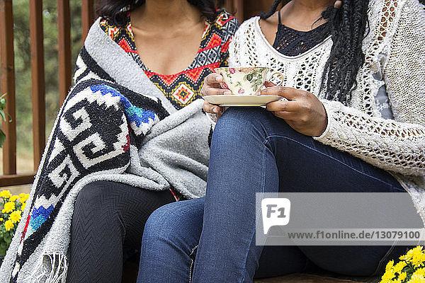 Mitschnitt einer Frau  die ein Getränk hält  während sie mit ihrer Schwester auf der Veranda sitzt