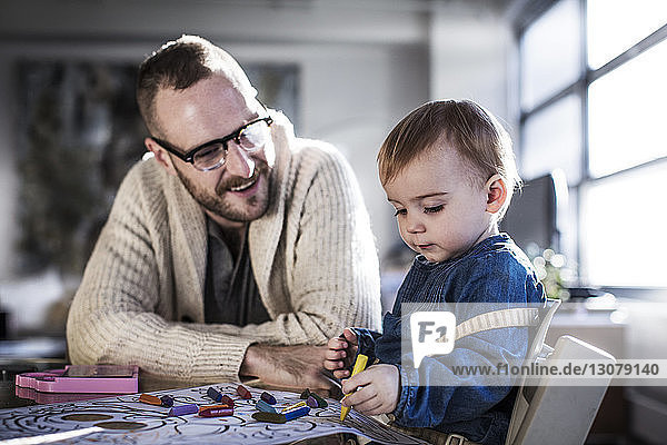 Smiling father talking while drawing with daughter at table