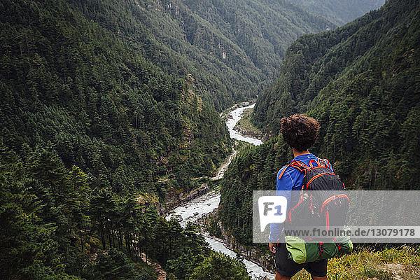 Rückansicht eines Wanderers mit Rucksack  der auf dem Berg steht