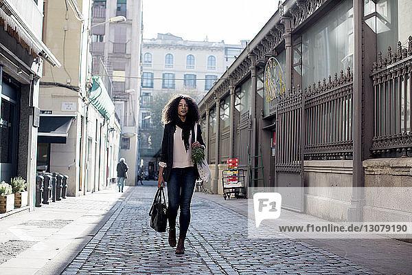 Frau geht auf der Stadtstraße inmitten von Gebäuden