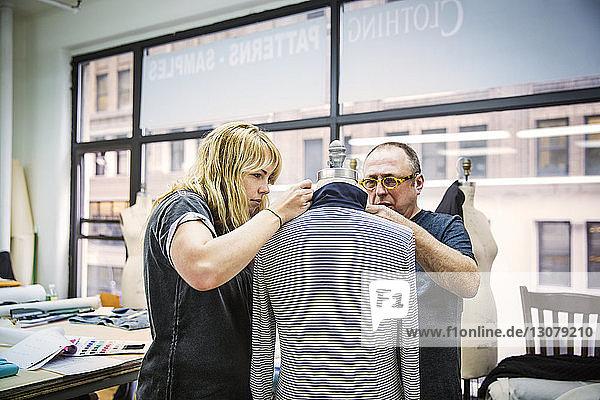 Modedesigner arbeiten im Designstudio an Jacke gegen Glasfenster