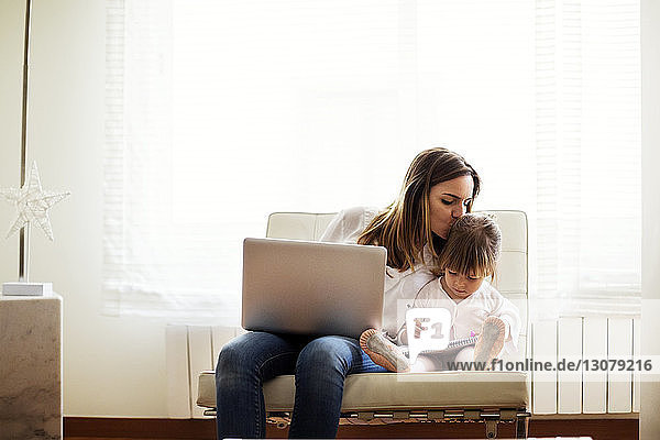 Mother kissing girl while sitting on chair at home