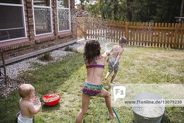 Baby girl looking at sister spraying water on shirtless brother through hose