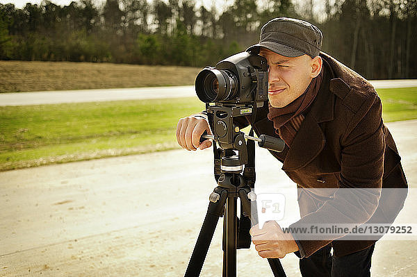 Photographer with tripod on road against forest
