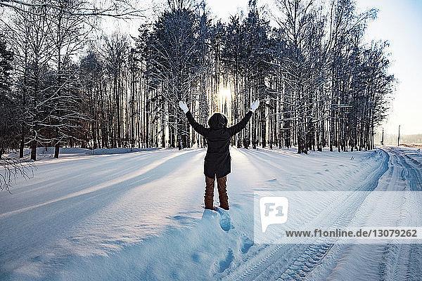 Rückansicht einer Frau  die mit erhobenen Armen auf einem schneebedeckten Feld steht