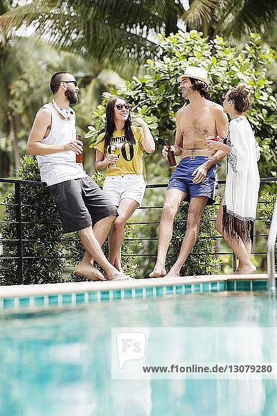 Männliche und weibliche Freunde unterhalten sich bei einem Drink am Pool