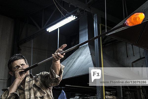 Mann bläst geschmolzenes Glas mit Rohr in der Fabrik Mann bläst geschmolzenes Glas mit Rohr in der Fabrik