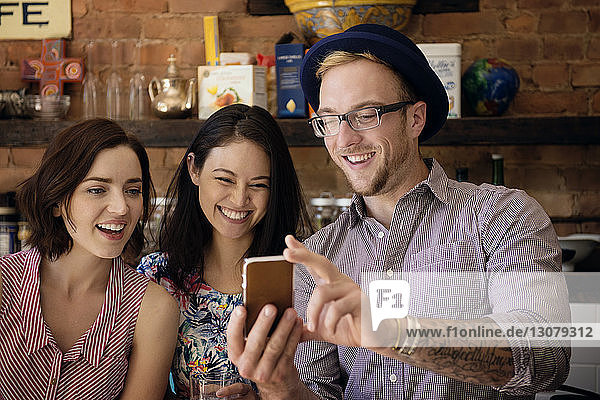 Man showing phone to female friends while standing at kitchen counter