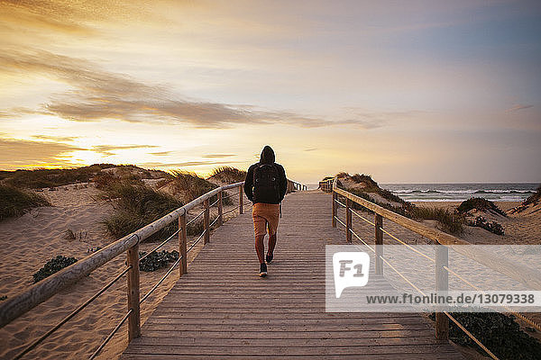 Rear view of hiker walking on footbridge at beach against sky during sunset